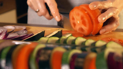 Young woman cutting juicy red tomato Footage
