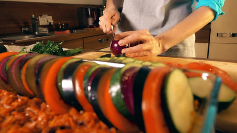 Woman cutting red onion and cooking ratatouille Footage