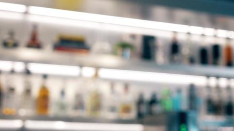 Blurred liquor bottles on backlit bar shelves Footage