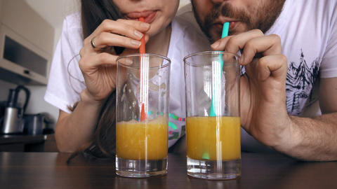 Young woman and man drinking orange juice with straws. Healthy lifestyle or Footage