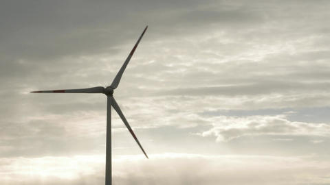 Wind turbine over stormy cloudy sky using renewable energy to generate Footage