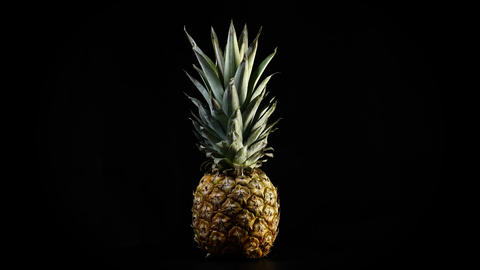 Pineapple rotating on black background Footage