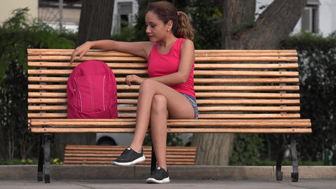 Female College Student Resting On Park Bench Live Action