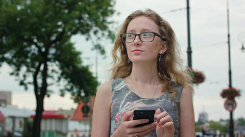 A Beautiful Redhead Using a Mobile Phone Outdoors Filmmaterial