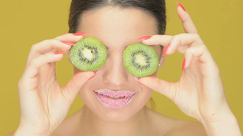 Playful woman with kiwi fruit eyes Stock Video Footage