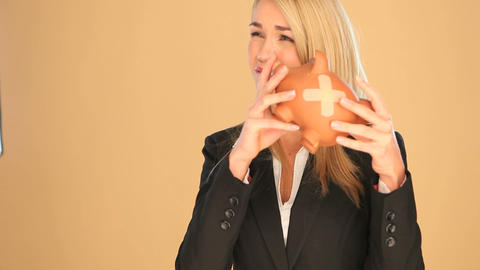 Blonde businesswoman with a piggybank Stock Video Footage