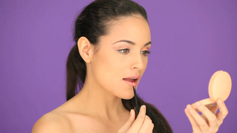 Beautiful woman applying lipgloss Stock Video Footage