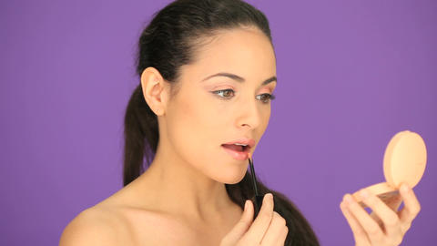 Beautiful woman applying lipgloss Stock Video Footage