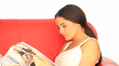 Woman reading a magazine on a sofa Stock Video Footage