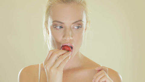 Attractive blonde woman eating a strawberry Footage