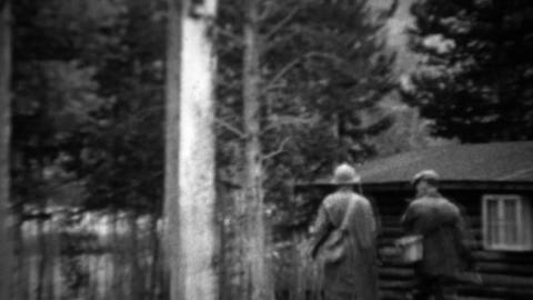 1934: Couple leaving rural log cabin for vacation fishing spot Footage