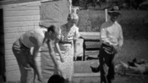 1934: Family plays with dog while man casually feeds chickens Footage