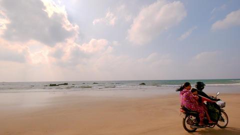 Burmese family rides on motorbike along tropical ocean sandy beach.Myanmar Footage