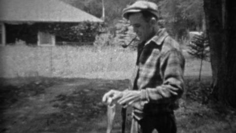 1935: Man smoking pipe proudly holding up freshly caught trout fish Footage