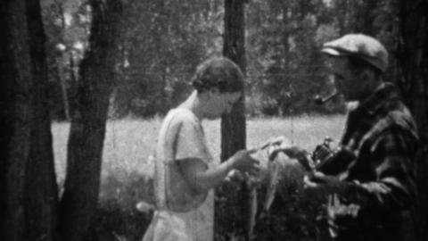 1935: Man photographs woman holding up recently caught trout fish Footage