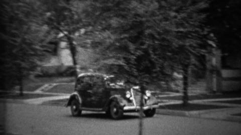 1935: Classic new black Plymouth car driving residential neighborhood Footage