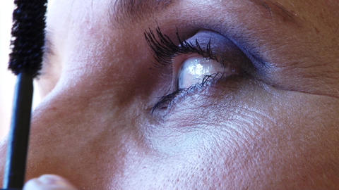 Beautician stretch mascara on long eyelashes of a woman 52 Footage