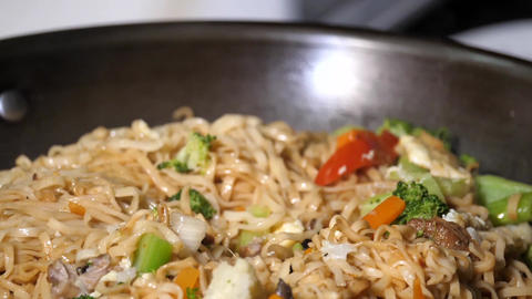 Slow motion of woman cooking stir-fried noodles with vegetables Footage