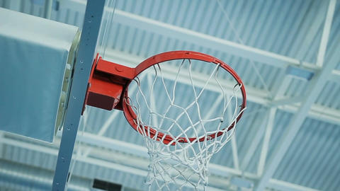 Closeup Camera Rotates under Basketball Hoop Located in Gym Footage