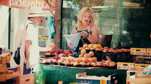 PULA, CROATIA - AUGUST 4, 2017. Woman selling peaches at local marketplace Footage