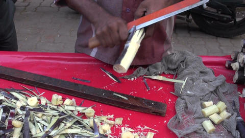preparing sugarcane pieces in Mumbai market, India Footage