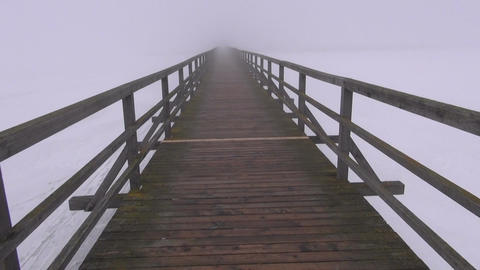 walking on empty old wooden winter bridge and early morning fog mist Footage