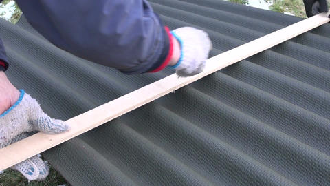 workers measure and marks roof sheet Live Action
