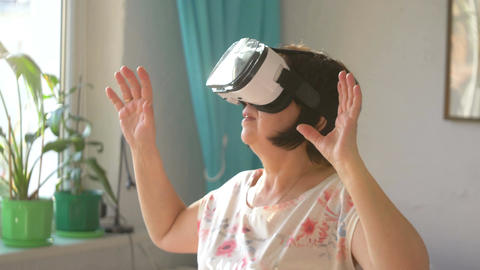Video of woman wearing virtual reality glasses and playing games at home in slow Footage
