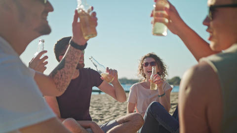 Young People Clinking Bottles on the Beach GIF
