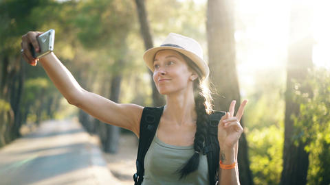 Funny tourist girl in hat taking selfie photos with smartphone camera during Filmmaterial