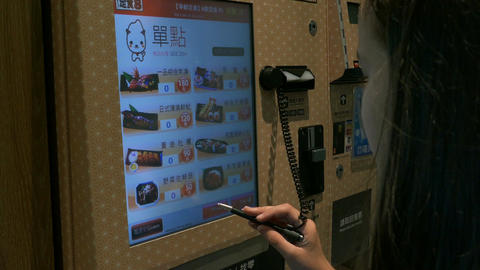 Young girl using Japanese style Automated machine to order food Footage