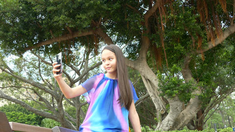 Young girl on bench taking selfie front Footage