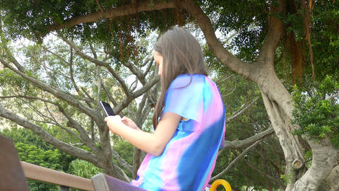 Young girl on bench taking selfie rear Footage