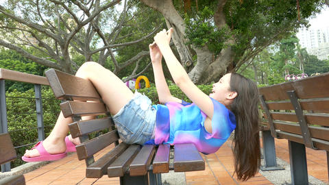 Young girl on bench taking selfie Footage
