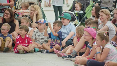 Kids and Mothers Watching Street Performance Image