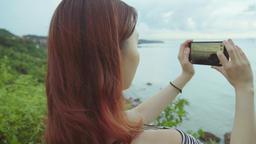 girl taking photo on the beach. Handheld shot Footage