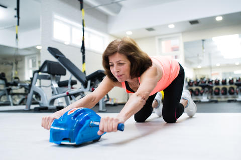 Senior woman in gym exercising abs with wheel roller Foto