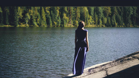 Beautiful young woman in long dress standing on shore near lake Footage