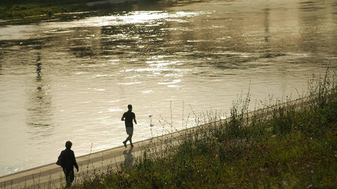 Enjoying a morning run. Man running along the riverbank Footage