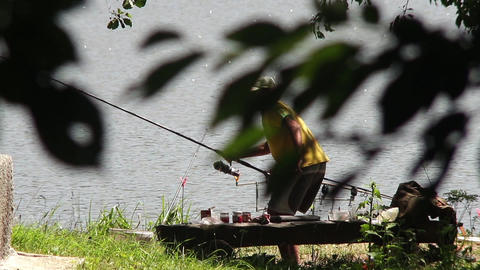 Fisherman who sits on the lakeshore and check all the time if any cork goes to t Footage