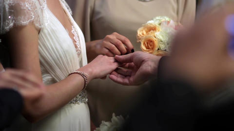 Godmother puts a ring on bride 's finger during religious ceremony 96 Footage