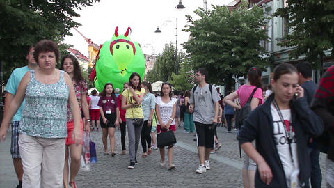 Inflatable caterpillar set in motion by unknown people walking on the main stree Footage
