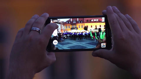 Man filming with mobile phone brass band that comes out of the town square, afte Footage