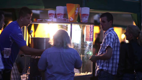 Man waiting in a popcorn stalls command that gave it while people walked around  Footage