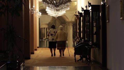 Older women walking down a hotel hallway 50 Footage