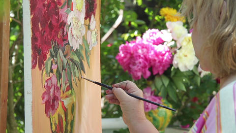 Painter draws in oil colors're a bunch of peonies in a vase on the table beside  Footage