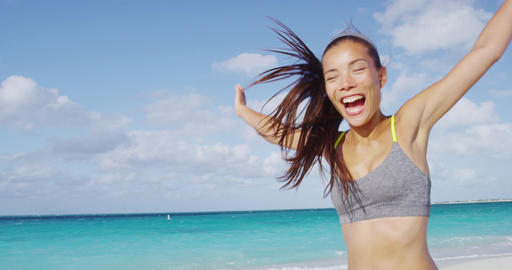 Happy sporty woman running having fun cheerful on beach vacation Footage
