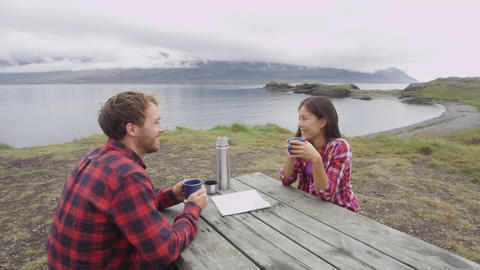 Camping couple sitting at table drinking coffee by lake on Iceland Footage