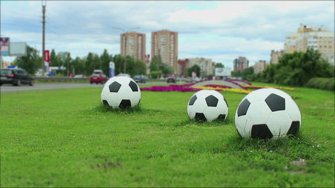 Three soccer balls by the road Filmmaterial