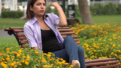 Female Teen Sitting On Park Bench Live Action